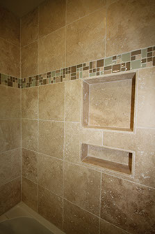 Shower stall stone tiling with inset glass mini tiles.